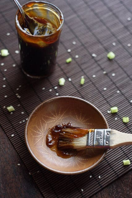 basting brush with thick sticky teriyaki glaze in a small dish