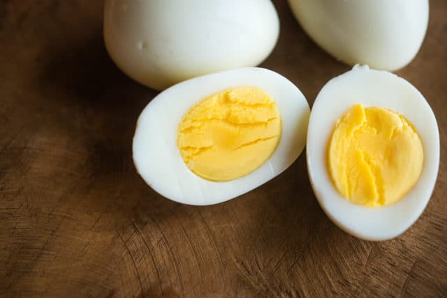 one peeled hard boiled egg cut open with two peeled hard boiled eggs behind on a wooden background