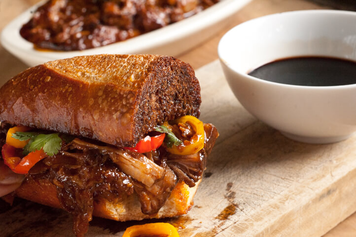 BBQ Balsamic Pulled Pork Sandwiches. Simmered all day in sweet and spicy barbecue sauce, piled on a butter crisped bun with caramelized sweet peppers and dipped into tangy balsamic vinegar.