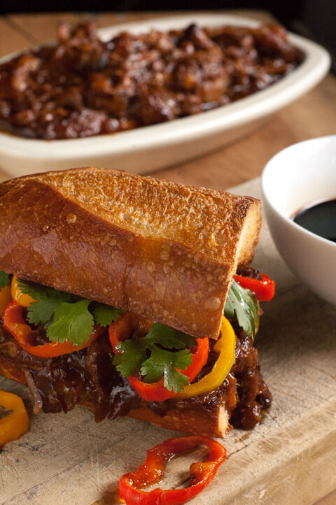 Balsamic BBQ Pulled Pork Sandwiches. These cook in your slow cooker all day in sweet and spicy barbecue sauce, then get piled on a butter crisped bun with caramelized sweet peppers and dipped into tangy balsamic vinegar.