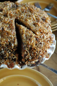 Toasted Coconut German Chocolate Cake Recipe. Toasting the coconut and adding rum to the frostings take this cake to a whole new level!   www.TheAdventureBite.com